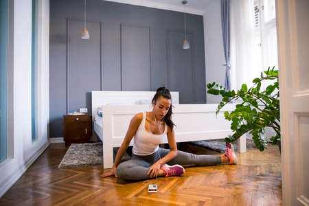 Pretty young fit woman choosing right musing for the exercises at home