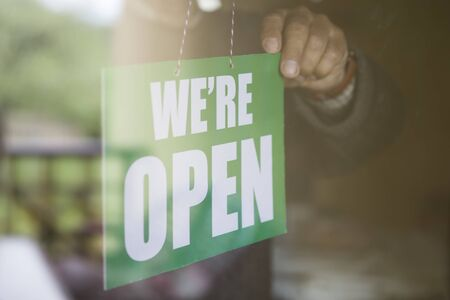 Closeup of the business owner hanging an open sign at a glass door