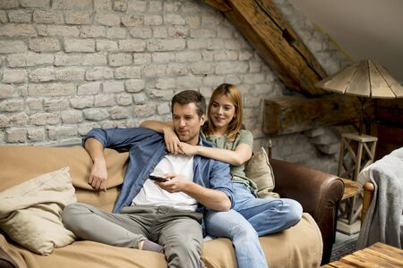 Beautiful young couple using remote control whi�e watching TV at home