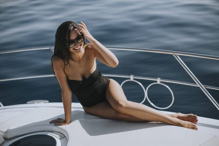 Pretty young woman in swimwear and sunglasses sitting on a yacht deck