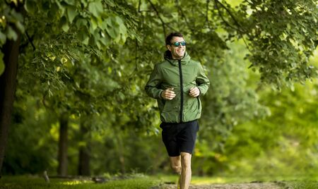 Athletic handsome young man running while doing workout in sunny green park Фото со стока - 147040944