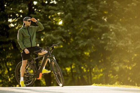 Handsome young man with ebike, mountain bike with electric battery in the park