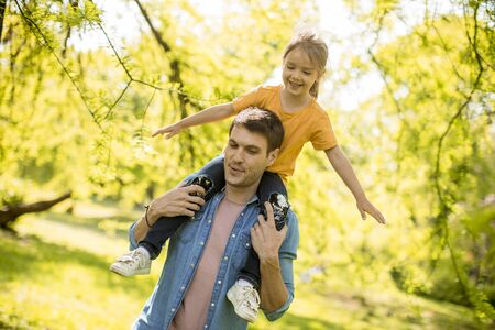 Cute little girl sitting on father shoulders in the park on a sunny day