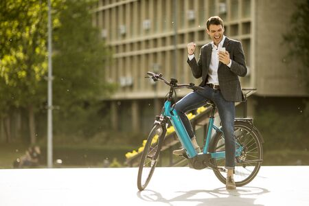 Handosme young businessman on the ebike received gret news by mobile phone Zdjęcie Seryjne