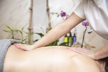 Young woman relaxing during back massage at the spa center