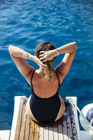 Rear view at young woman relaxing on the yacht on sea at sunny day