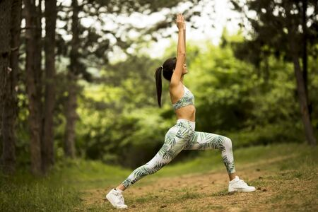 Pretty young woman stretching and breathing fresh air in middle of forest while exercising