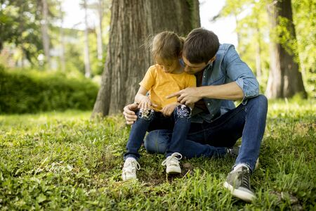 Single father sitting on grass by the tree with cute little daughter
