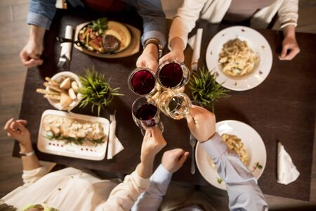 Four hands with red wine toasting over served table with food in the restaurant 版權商用圖片 - 148096482