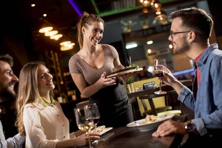 Pretty waiter woman serving group of friends with food in the restaura Stock Photo