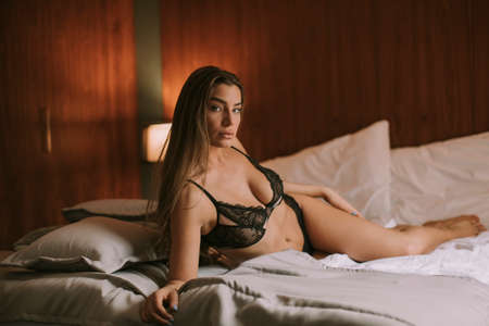 Pretty young woman in lingerie lying on the bed