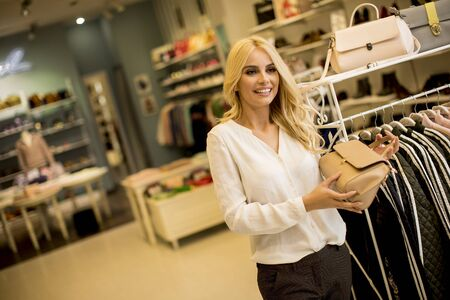 Pretty young woman buying purse in the fashion store Stock fotó