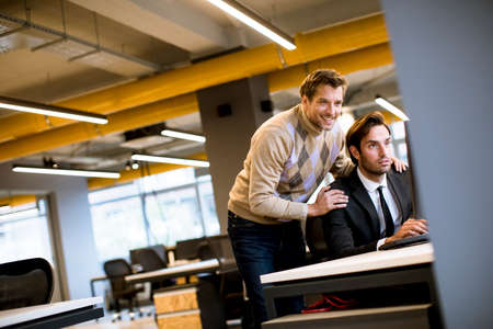 Two handsome young businessmen discussing in office by the table