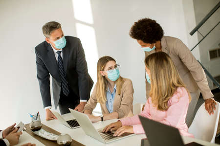 Group business people have a meeting and working in the office and wear masks as protection from corona virus Stock Photo