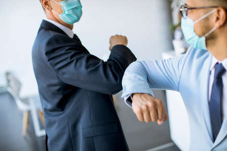 Two colleagues avoid a handshake when meeting in the office and greet with elbows bumping Standard-Bild