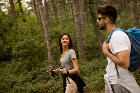 Smiling young couple walking with backpacks in the forest on a summer day
