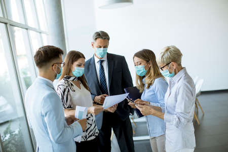 Business partners standing and looking at business results in the office while wearing face masks sa an virus protection
