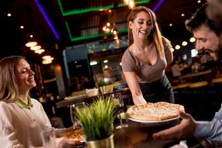 Pretty waiter woman serving group of friends with food in the restaurant