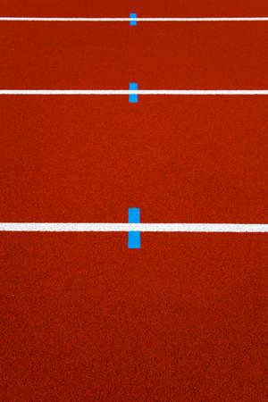 Closeup of the white lines on red stadium running track