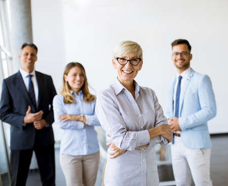 Group of a businesspeople standing together in the office with their mature female bussines leader