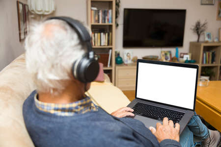 Modern elderly man siting at home with earphones and having online video call