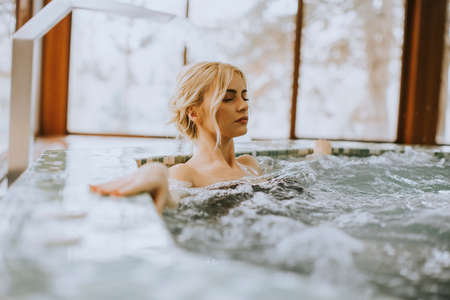 Pretty young woman relaxing in the whirlpool bathtub Stock Photo