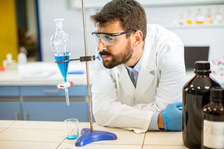 Researcher working with blue liquid at separatory funnel in the laboratory Banco de Imagens