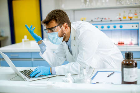 Handsome young researcher in white lab coat and protective mask working using laptop while sitting in the laboratory