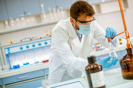 Handsome researcher in protective workwear standing in the laboratory and analyzing flask with liquid