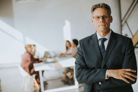 Confident handsome business man standing in the office