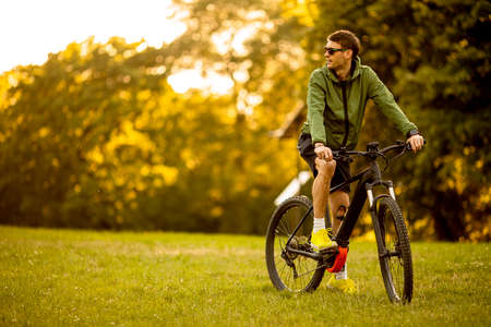 Handsome young man riding ebike in the park Stockfoto