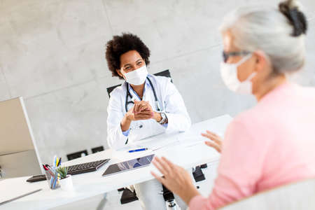 Senior woman with protective facial masks receive news from black female doctor in the office