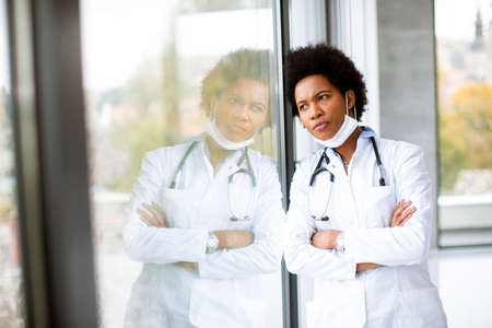 Black female doctor standing by the medical office window with negative expression