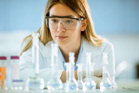 Young female medical or scientific researcher looking at a flasks with solutions in a laboratory