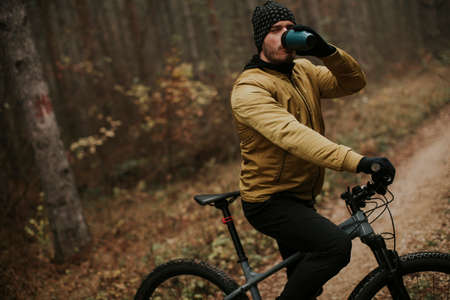 Handsome young man taking a brake during biking through autumn forest