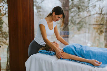 Beautiful young woman lying and having shoulder massage in spa salon during winter season
