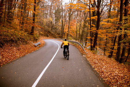 Handsome young man biking on a country road through autumn forest