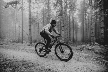 Handsome young man biking through autumn forest