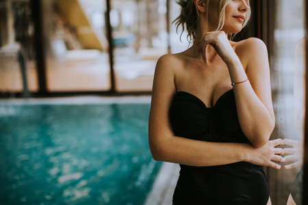 Beautiful young woman standing by the window at indoor swimming pool