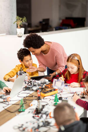 Smily African American female science teacher with group of kids programming electric toys and robots at robotics classroom Stock Photo