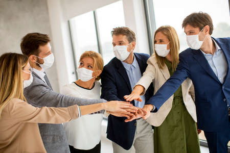 Group of business people with protective facial masks holding hands together in the office