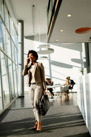 African American business woman with bag using mobile phone and walking in the office Imagens