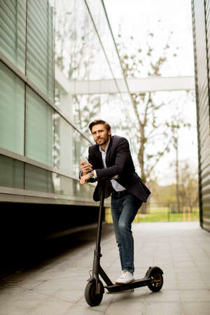 Handsome young businessman using mobile phone on electric scooter