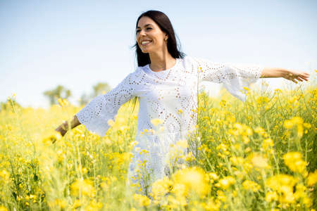 Pretty young woman in the rapeseed field