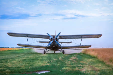 Landing of agricultural airplane to the meadow between wheat fields. Landing strip is bumpy. There is a puddle in front of the plane.