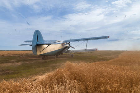 airstrip: Agricultural plane begins to accelerate before take off Plane stands on a wheat field. Propeller is rotating and making strong wind and loud noise. A lot of dust is in the air. Blue cloudy sky is in the background.