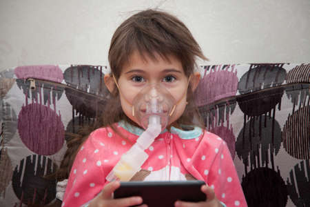Little girl is wearing a breathing mask and playing games on mobile phone. She is sick. Girl is inhaling medicine through inhaler at home. She dressed in dotted pink pajamas. Her disease is pneumonia.