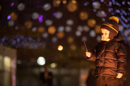 Little boy with a burned down sparkler on a blurred bokeh background Outdoors photography. Boy is looking at a sparkler in his hand.