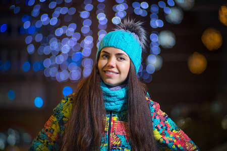 Young pretty woman is smiling and looking at camera Evening outdoors winter portrait.