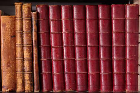 Row of old leather hardbound books on a shelf photo